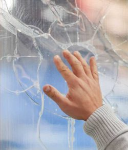 Hand touching a cracked glass pane